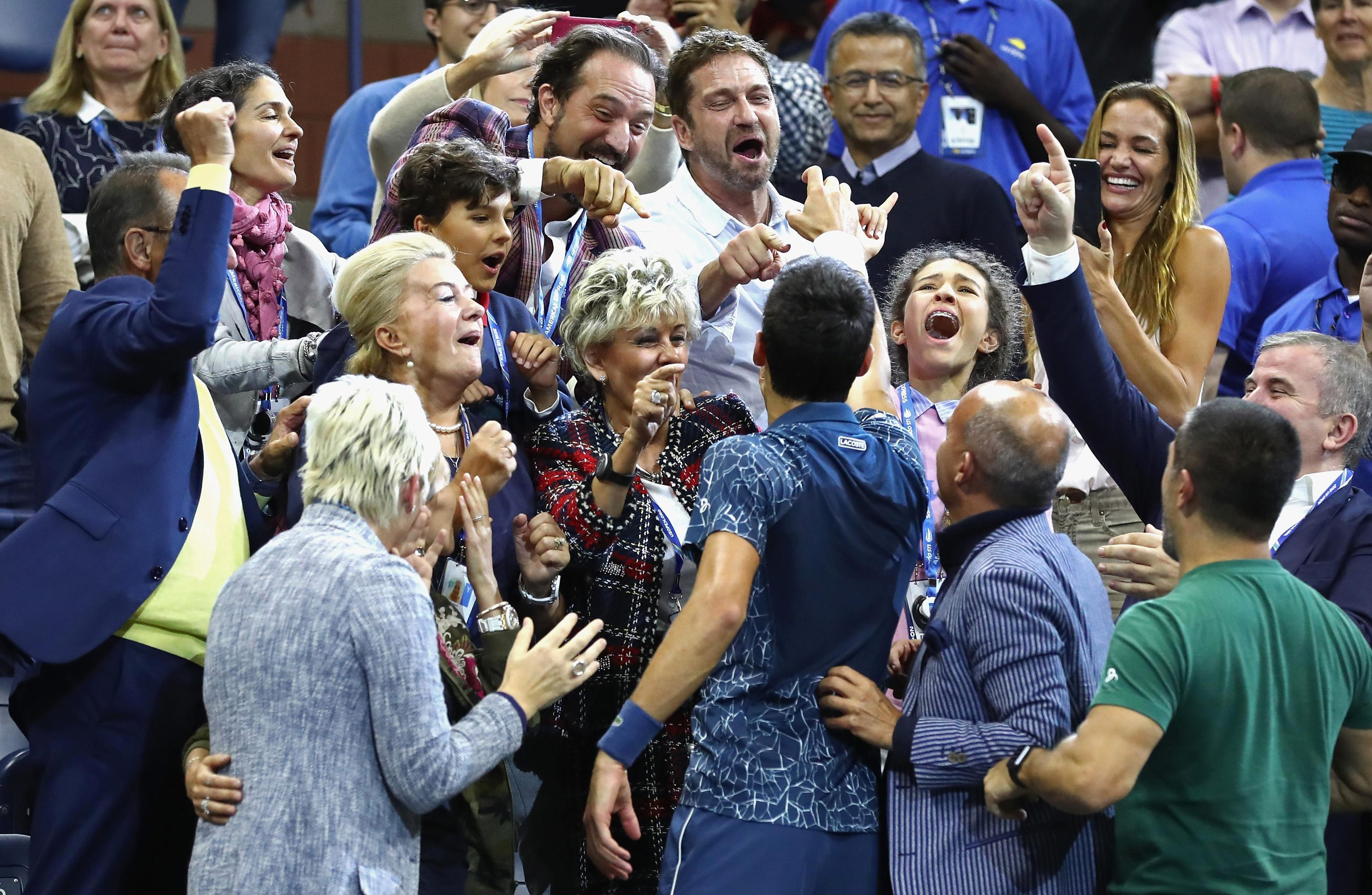 Novak Djokovic is congratulated by Hollywood actor Gerard Butler after winning the US Open
