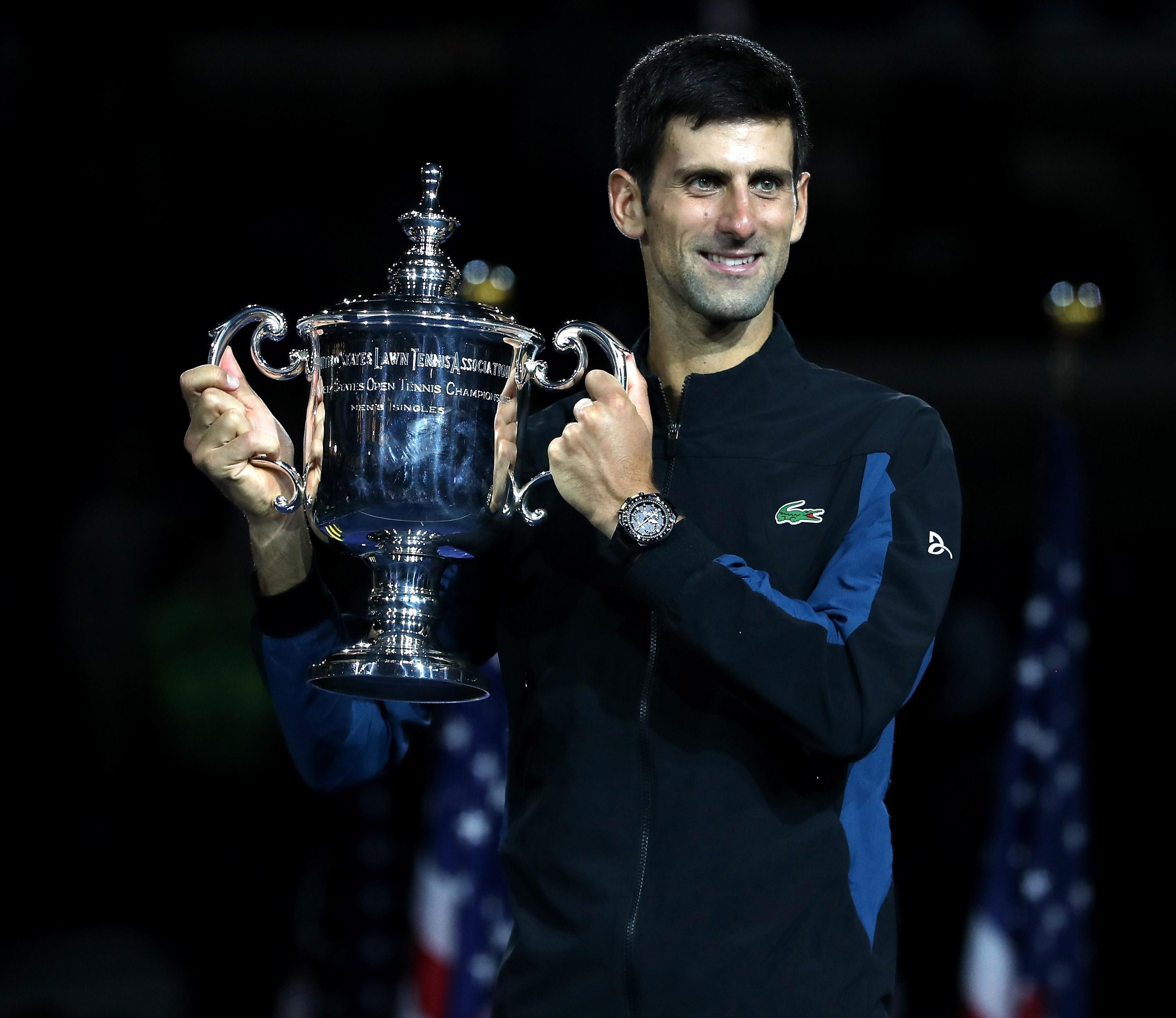 Novak Djokovic celebrates with the US Open trophy after beating Juan Martin del Potro
