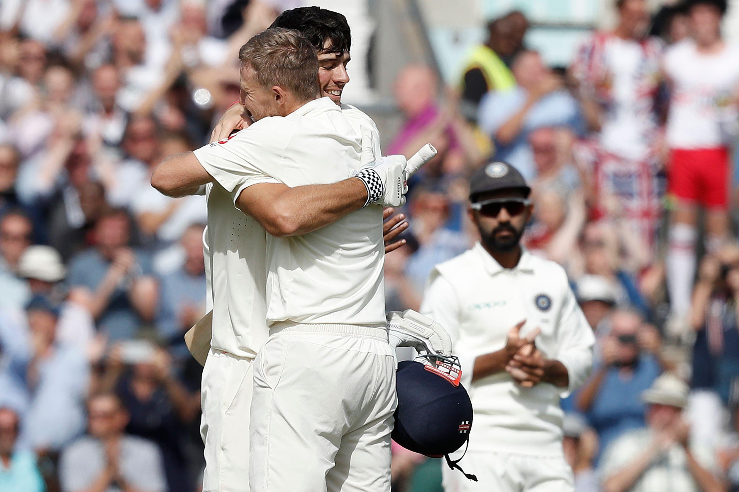 Previous captain Cook and current captain Root embrace as the former made his century