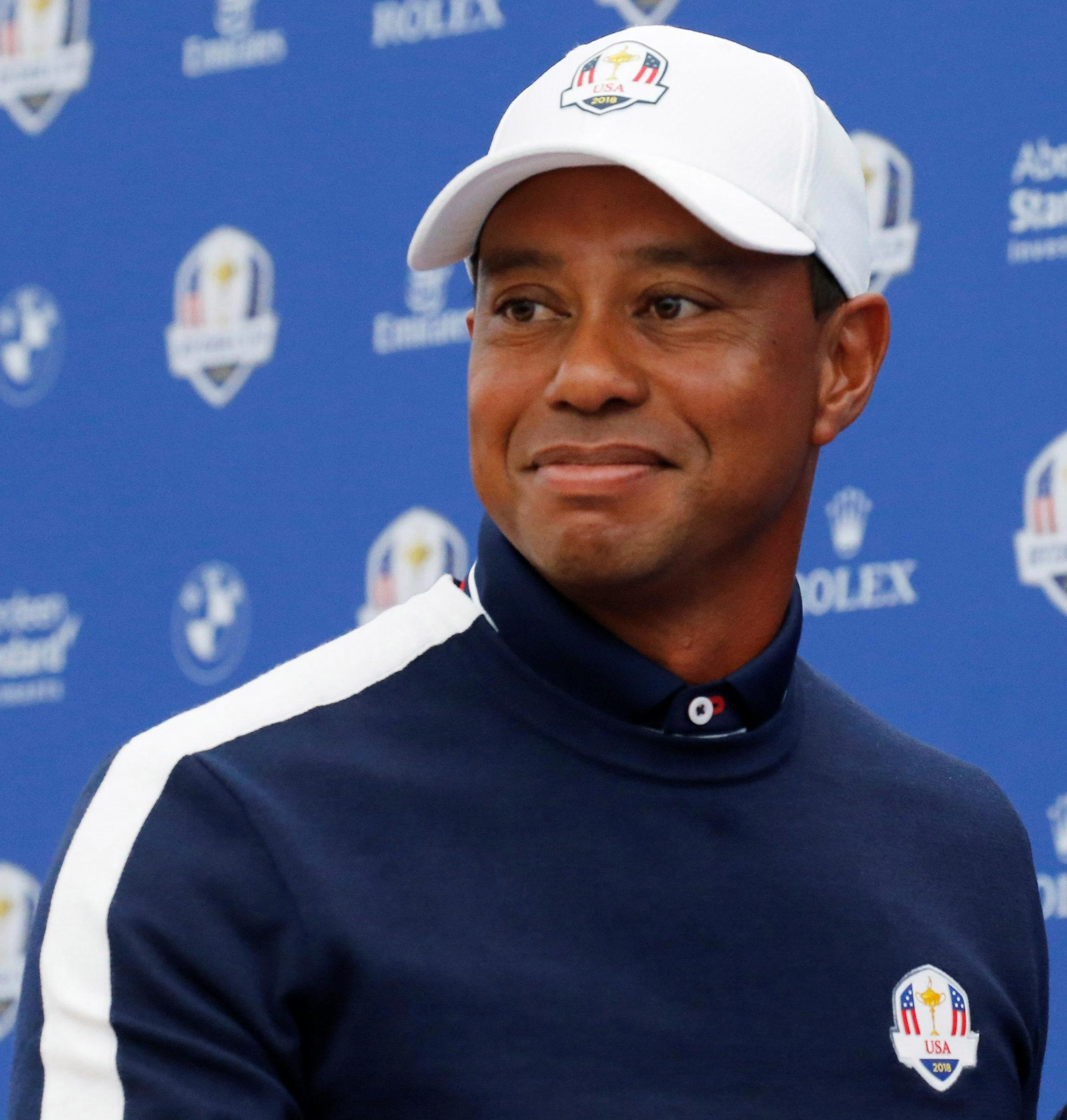 A smiling Tiger Woods faces the media at Le Golf National