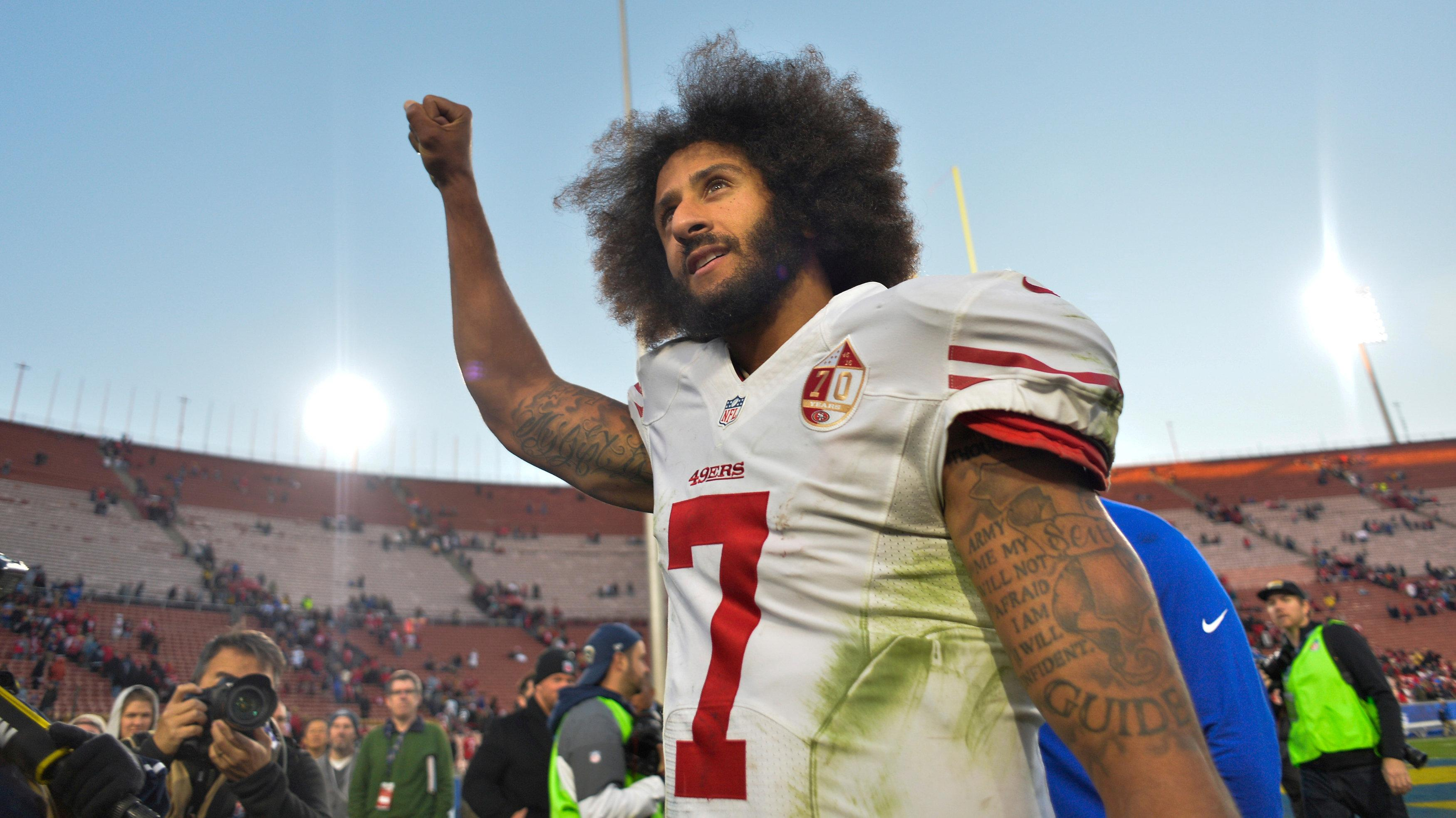 Kaepernick holds his right arm aloft after a game at the Los Angeles Memorial Colosseum