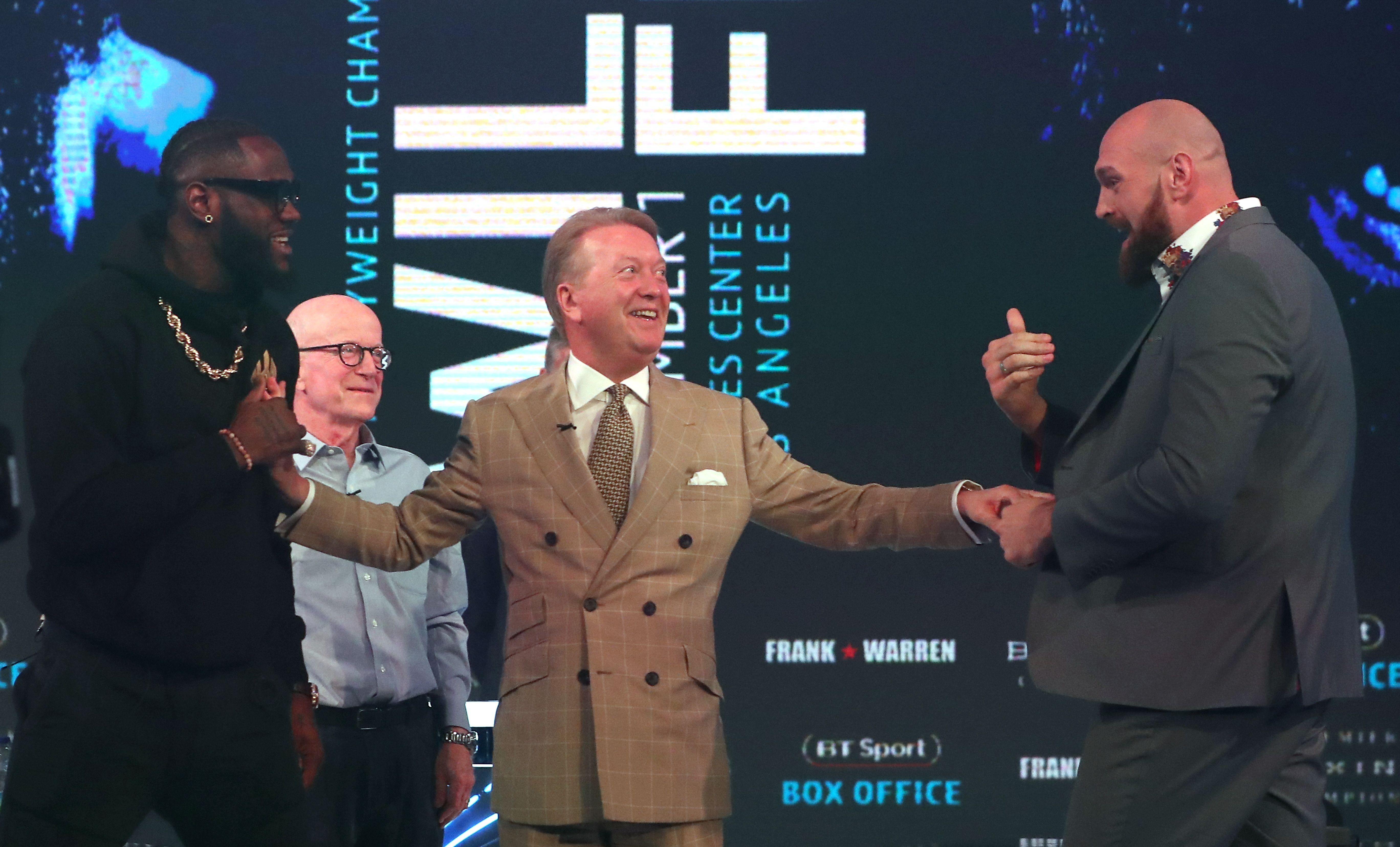 WBC world heavyweight champion, US boxer Deontay Wilder, and former world heavyweight champion, British boxer Tyson Fury are separated by boxing promoter and manager Frank Warren.