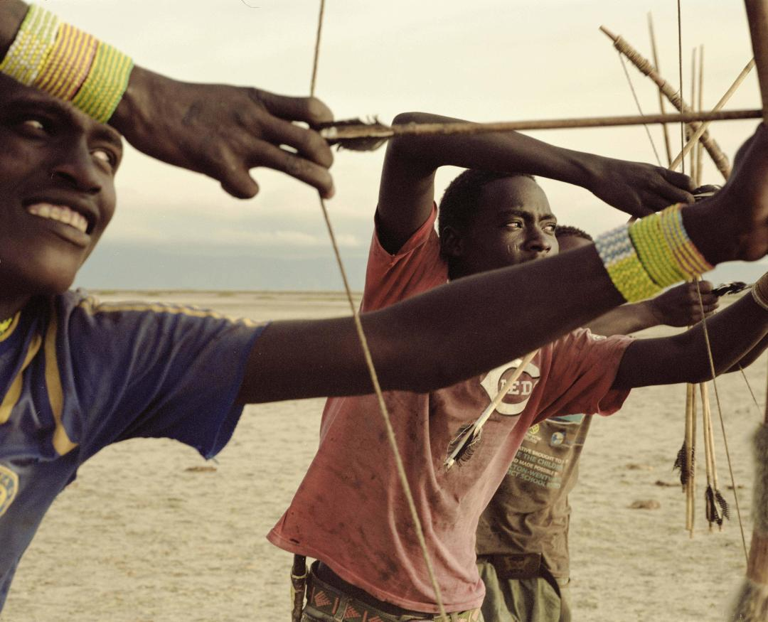 Young Hadza men test their daily hand-made arrows as they prepare for the hunt