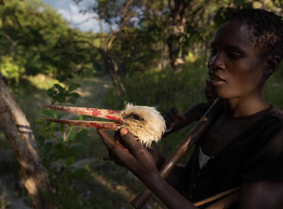 A Hadza hunter clutches the head of a hunted dead stork.