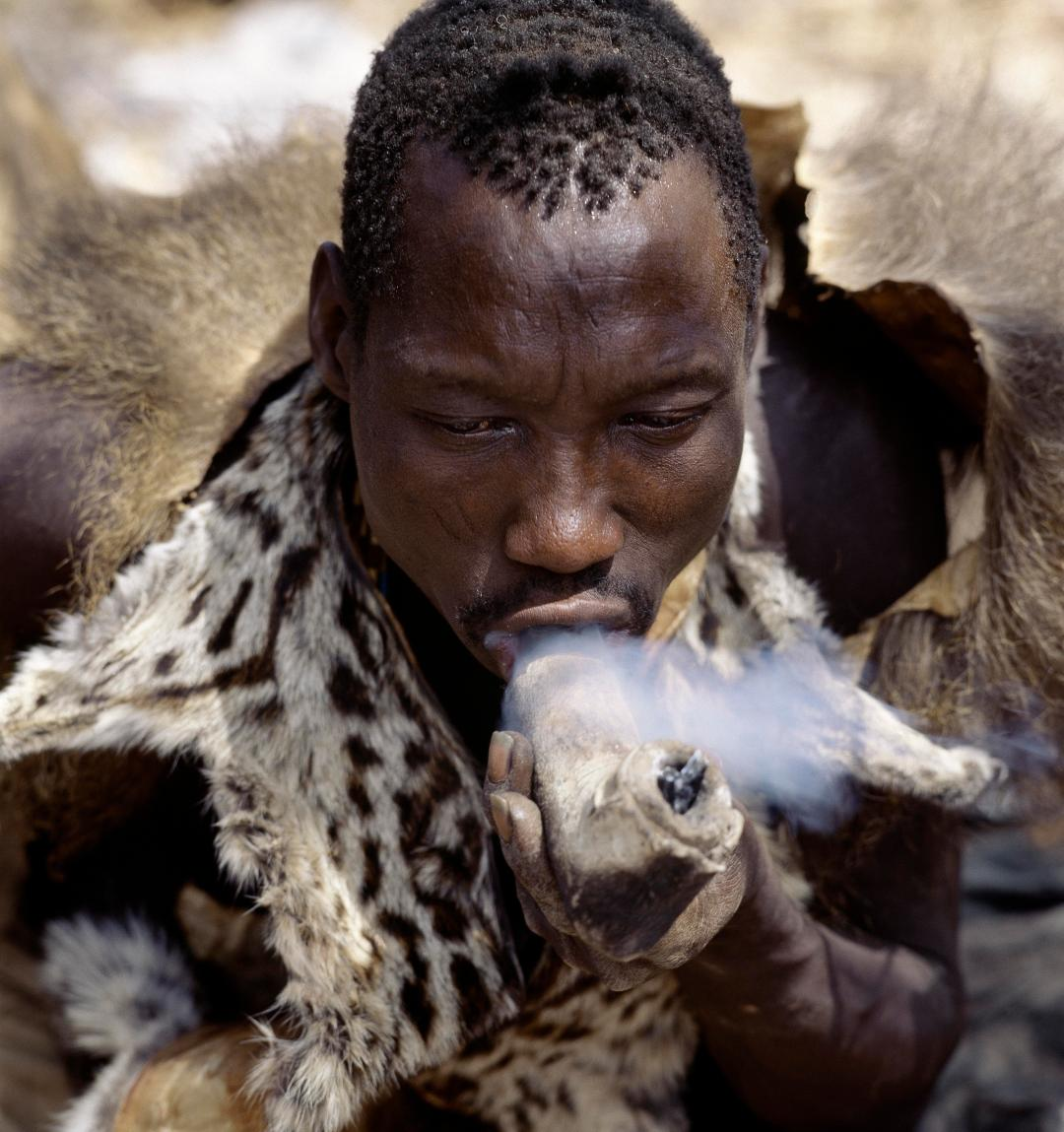 A Hadza hunter wearing a genet cat skin cape smokes cannabis from a crude stone pipe sheathed in leather