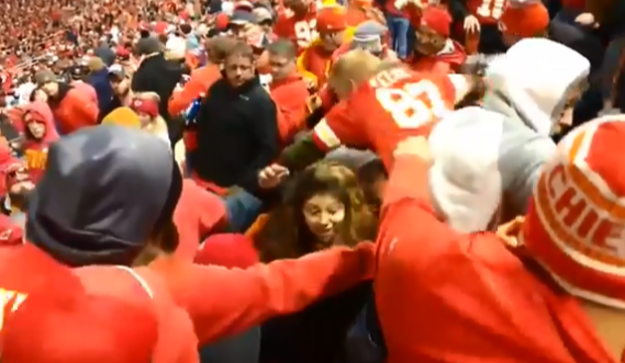 The female fan just about manages to escape the fracas