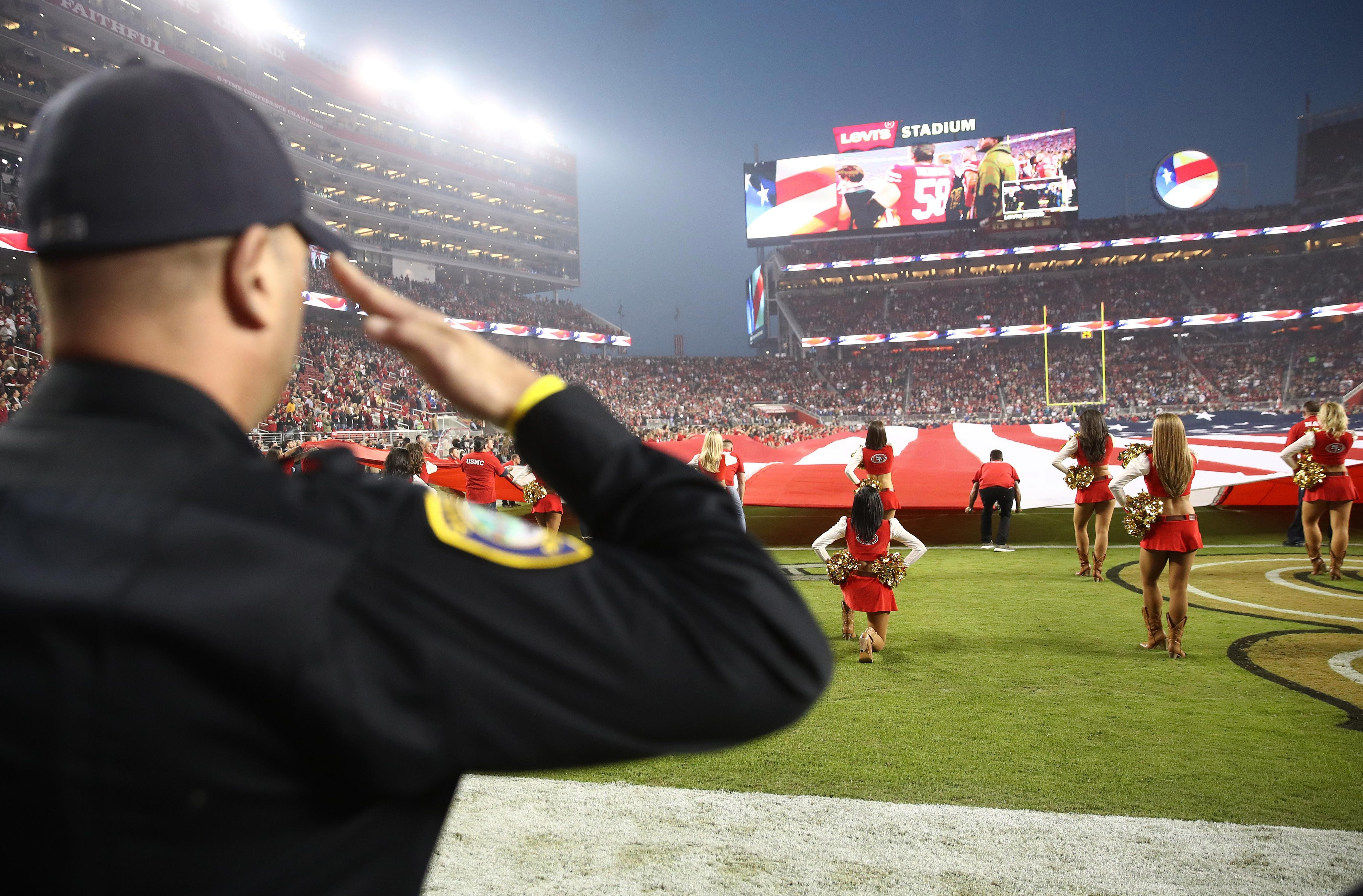 A man salutes the flag while Morris kneels