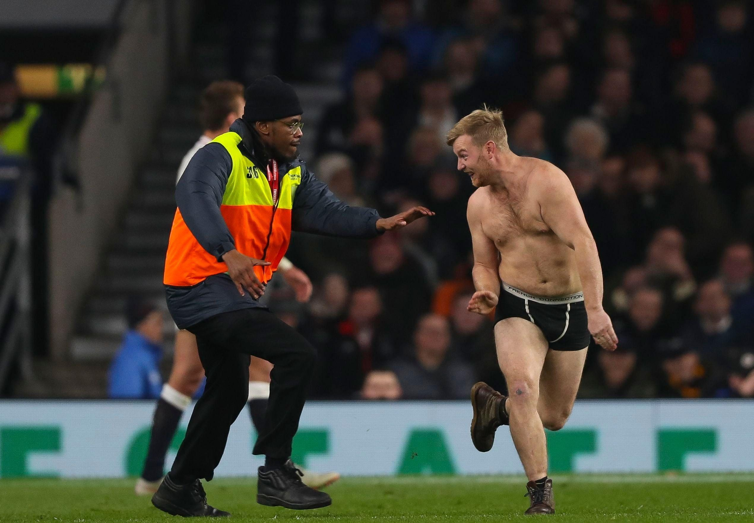 The streaker tries to escape the clutches of another steward