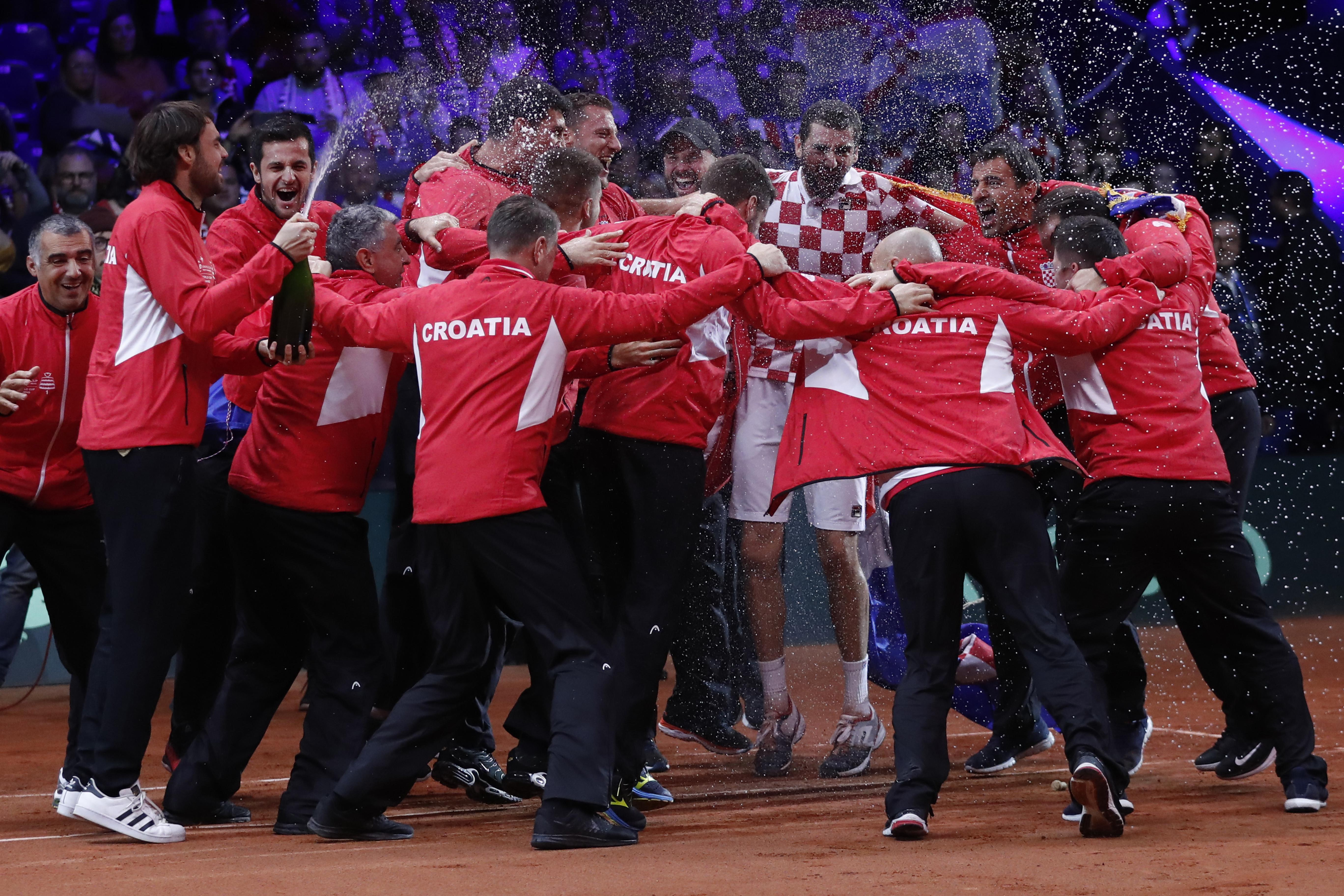 The Croatia team mobbed Cilic as he secured victory without dropping a single service game in six sets