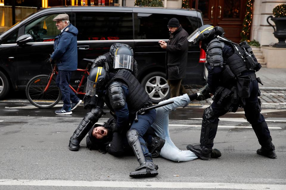 A men is arrested by riot police in the French capital