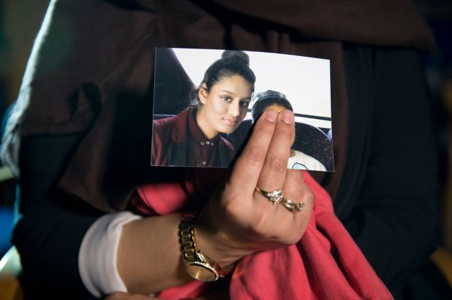 Renu, eldest sister of Shamima Begum, 15, holds her sister's photo while being interviewed by the media