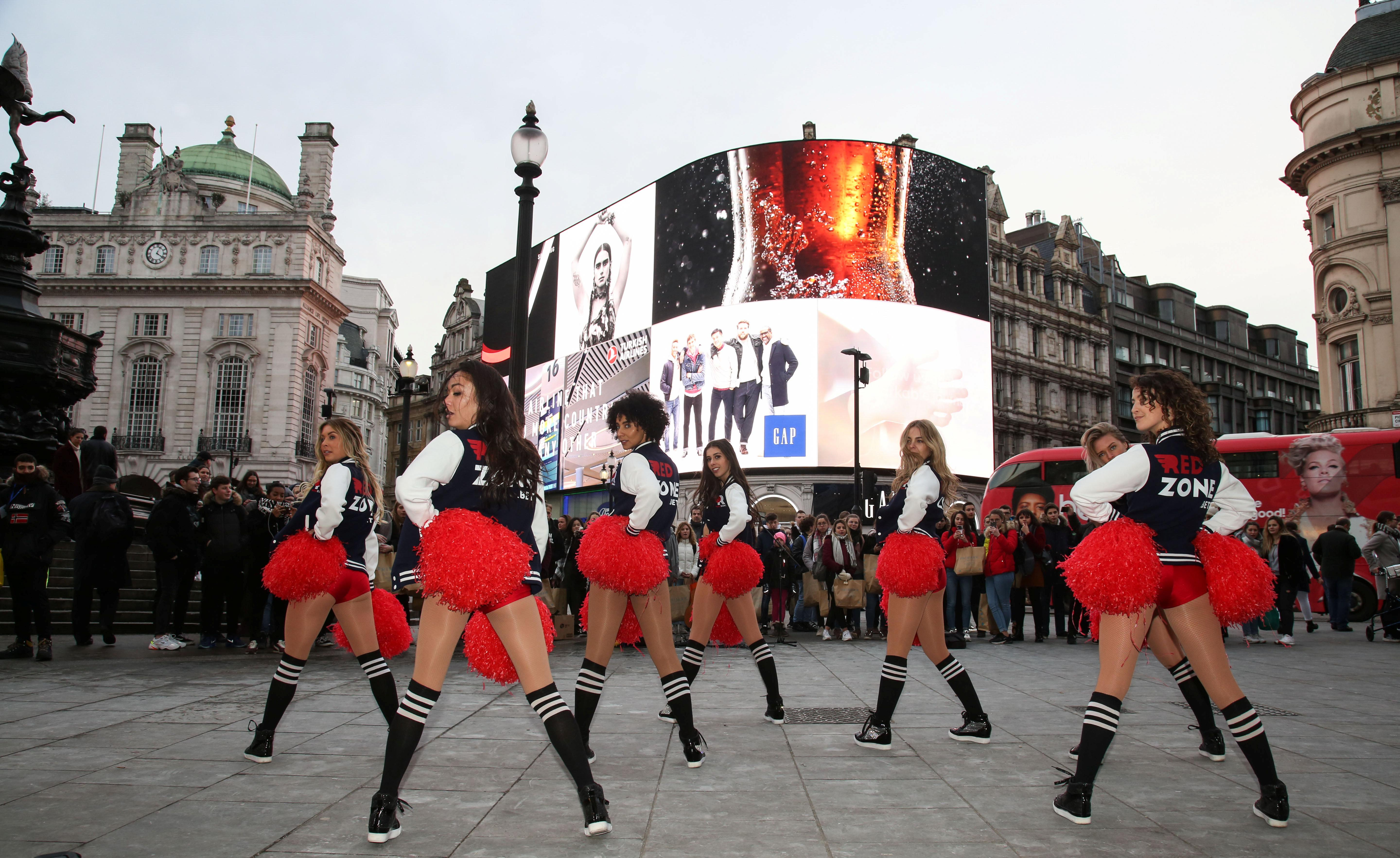 Cheerleaders draw crowds in central London as they perform