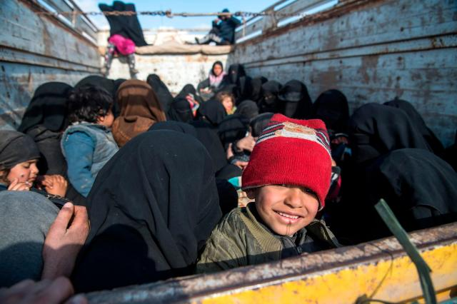 Women and children fleeing from the last Islamic State group's tiny pocket in Syria sit in the back of a truck near Baghuz, eastern Syria
