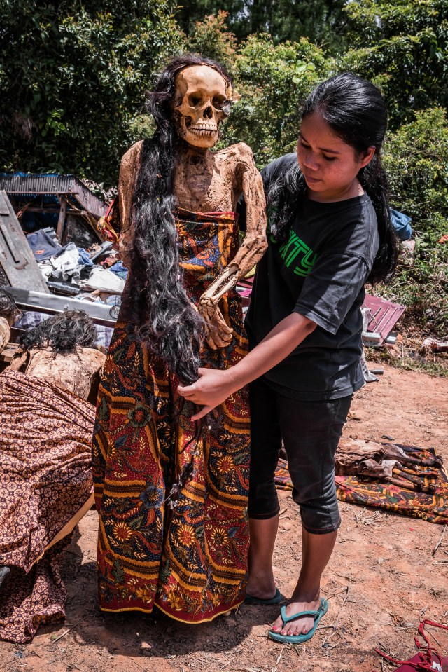 A mummy with long hair is tended to by a relative