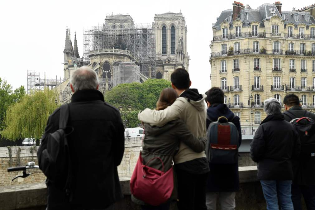 A couple hug as they look at the damaged cathedral