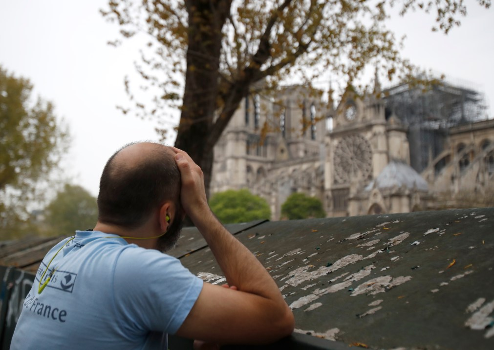 The sight of the damaged cathedral appears to be too much for one man