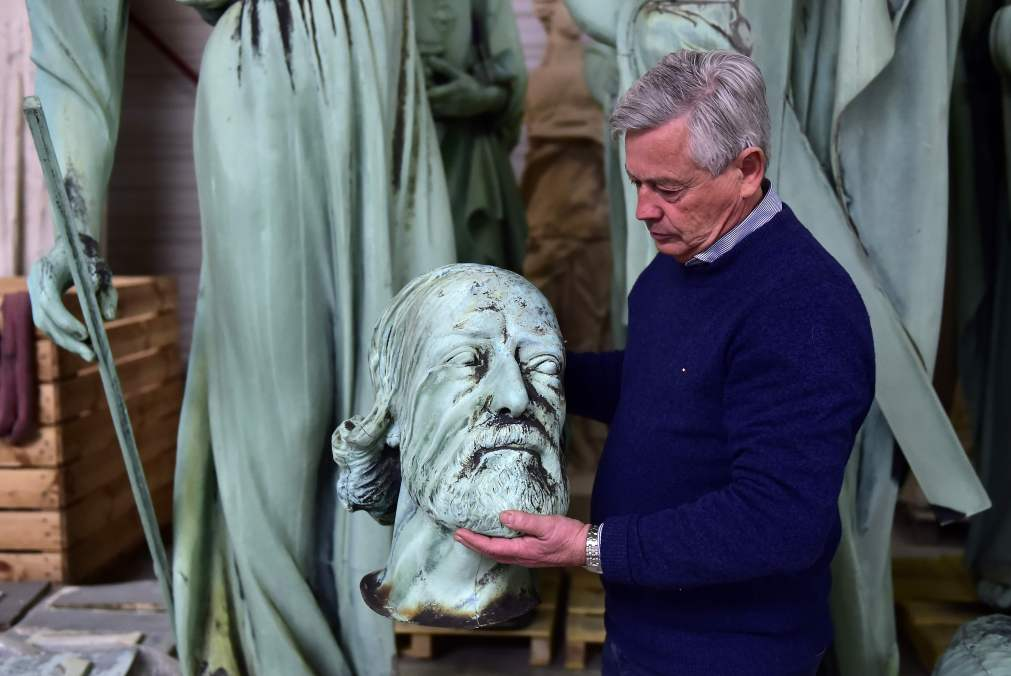 Mr Belem inspects the head of a statue that sat around the spire of the cathedral