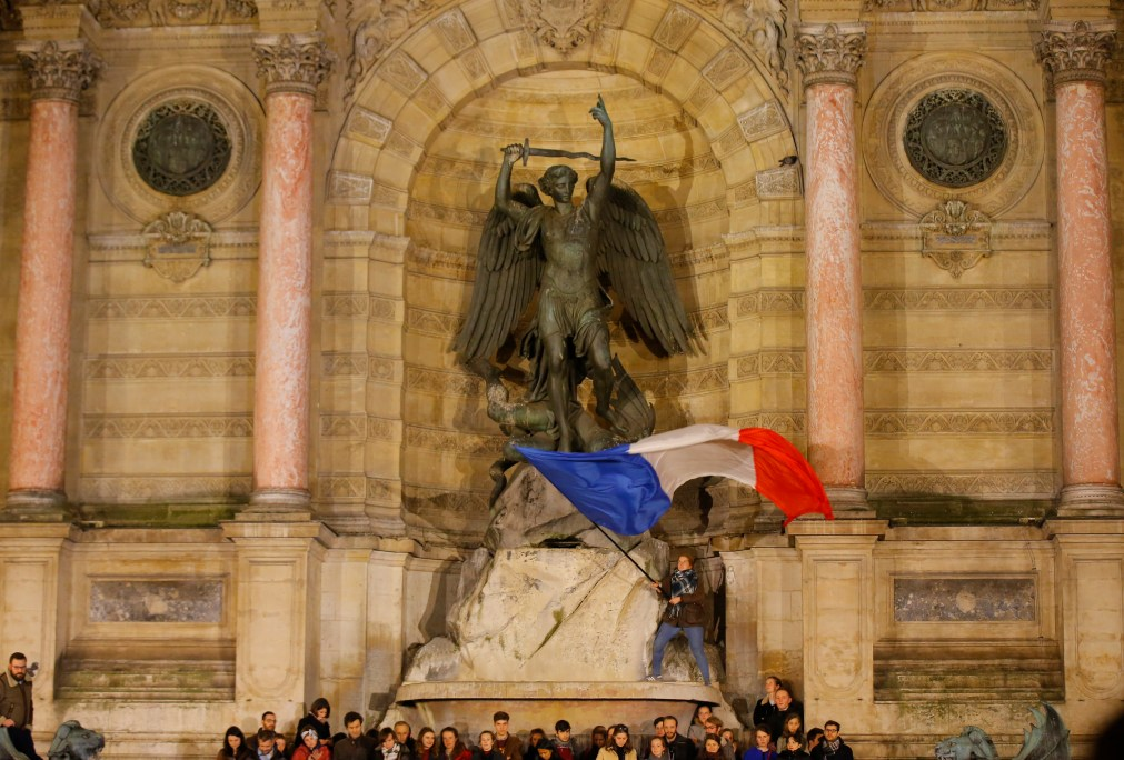 People gather at a vigil for the devastated cathedral in Paris