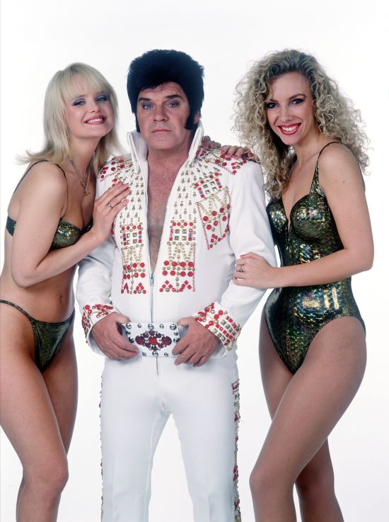 The star poses in an Elvis costume with some glamour girls