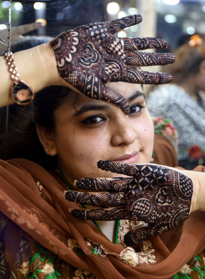 A Pakistani customer shows her decorated hands with henna designs at a beauty salon ahead of the Eid al-Fitr holiday, in Karachi