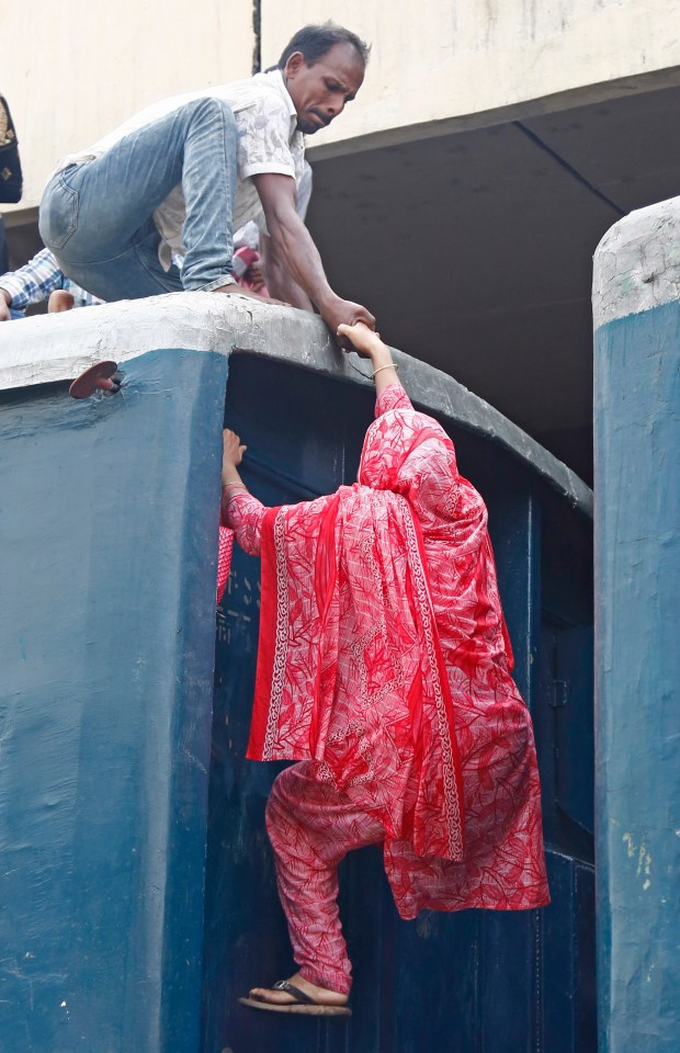 One woman is given a helping hand as she climbs up onto a train in Bangladesh