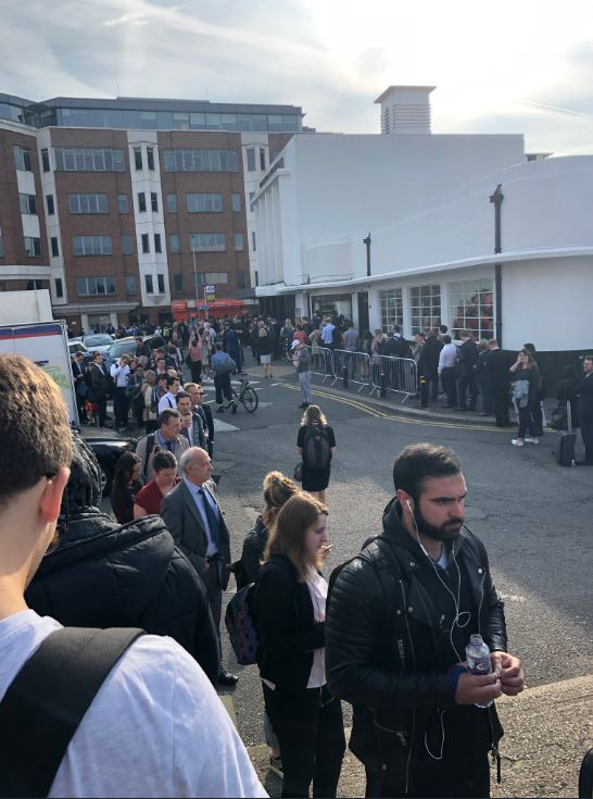 Commuters wait outside Surbiton station as one passenger described it as 'absolute choas'