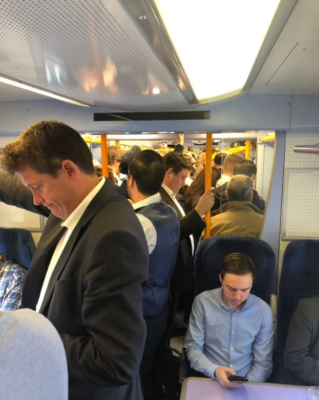 Passengers stand on a crowded train amid the first day of industrial action