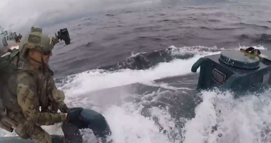 Helmet cam footage shows one guardsman jumping onto the sub and keeping his balance
