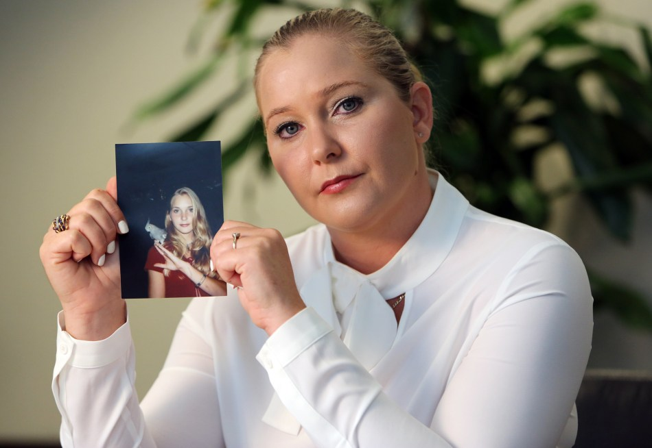 Virginia Roberts holds a photo of herself taken a year after she claims she was first abused by Epstein