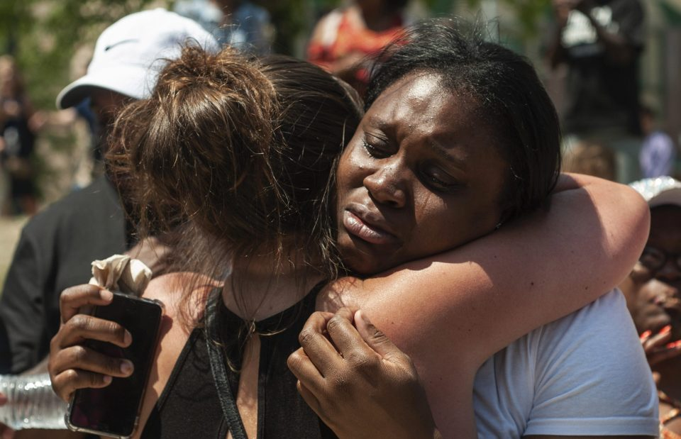 People console each other as they gather for a vigil in Dayton, Ohio