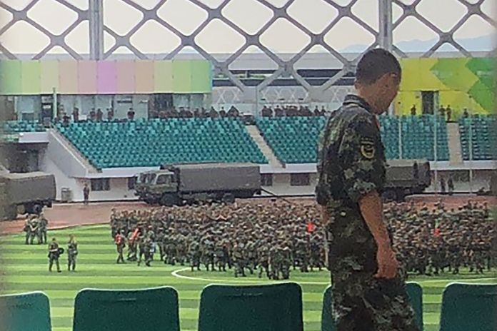 Chinese military personnel gather at the Shenzhen Bay stadium in Shenzhen
