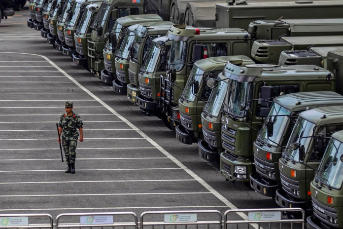 A member of People's Armed Police Force (PAP) walks by military vehicles