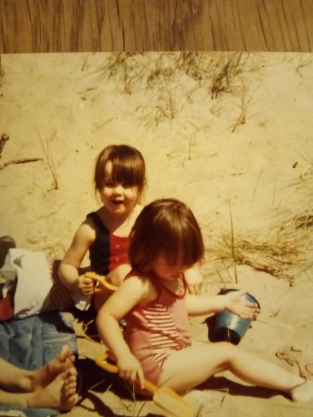 Michelle as a little girl with her sister Sarah on the beach