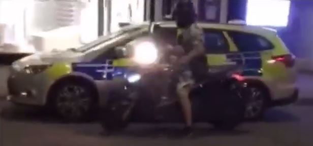 This thug smashes a parked police in this scene