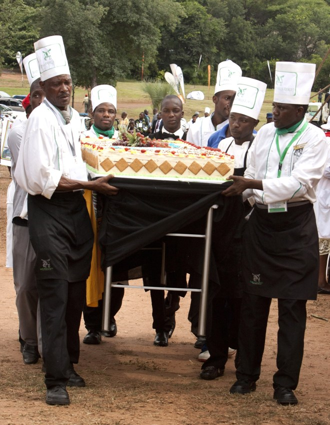 Catering staff carry a birthday cake for the celebration of Zimbabwean President Robert Mugabe's 91st birthday in Victoria Falls