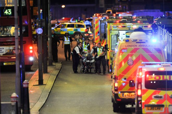 Paramedics can be seen rushing to treat someone hurt in the London Bridge attacks - with the new text alert trial hoping to improve public safety