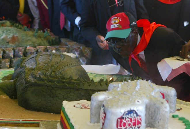 Robert Mugabe blows out candles on a cake made to look like a crocadile... earlier he and guests were eating the real thing
