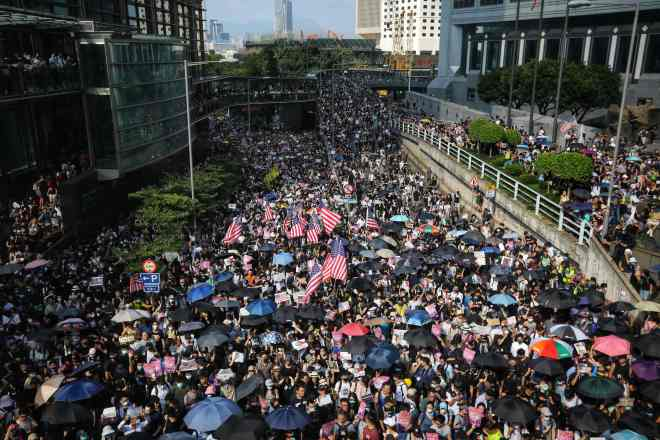 Protesters wave US national flags as they march from Chater Garden to the US consulate