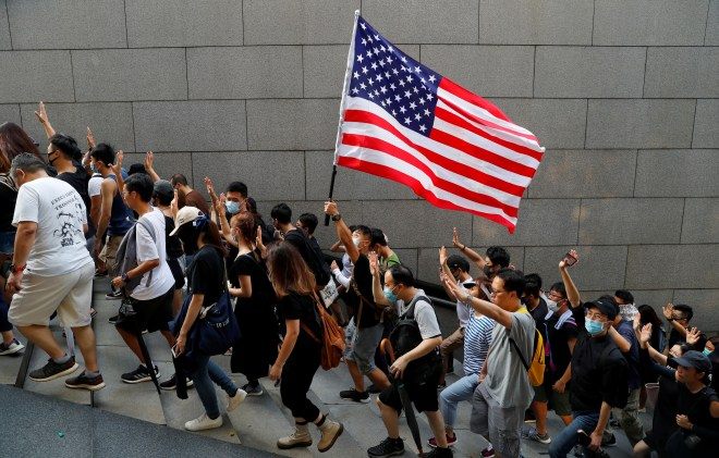 Protesters hold up five fingers and a US flag during a rally