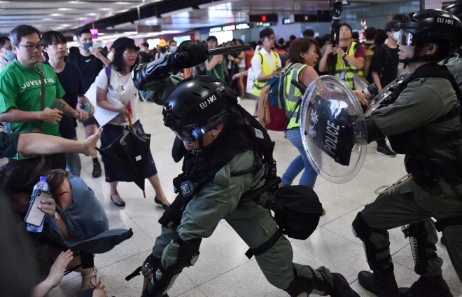 A police stands guard with a gun as protesters aim laser pointers at him outside the Mongkok Police Station