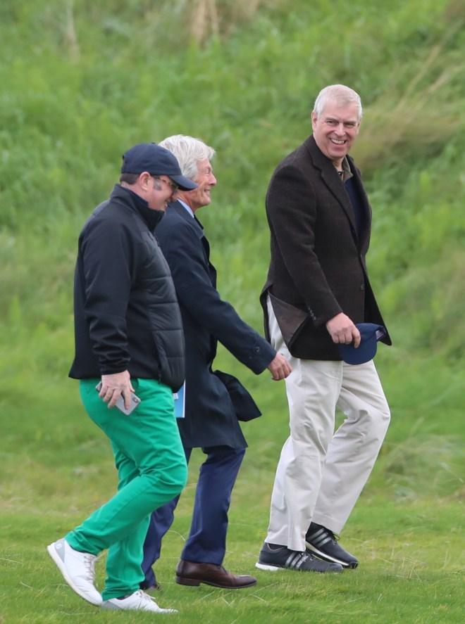 The Duke of York smiles as he walks along the green