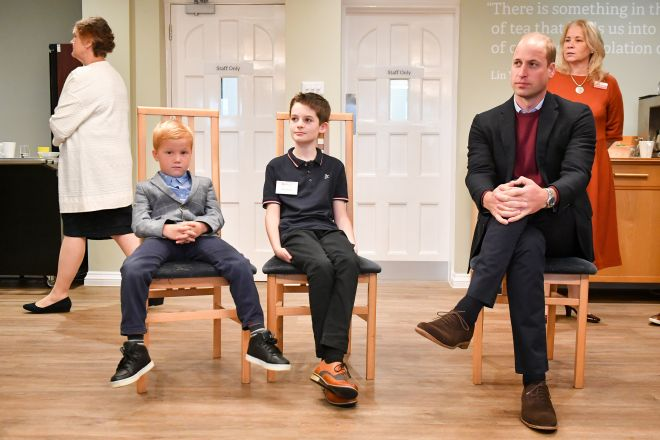 Joseph Dowden, six, slumps next to Prince William during the royal's visit to the Fire Fighters Charity's Harcombe House