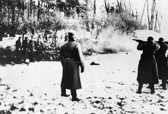 Polish men (left) watch helplessly as a Nazi firing squad picks their fellow prisoners off methodically, from right to left