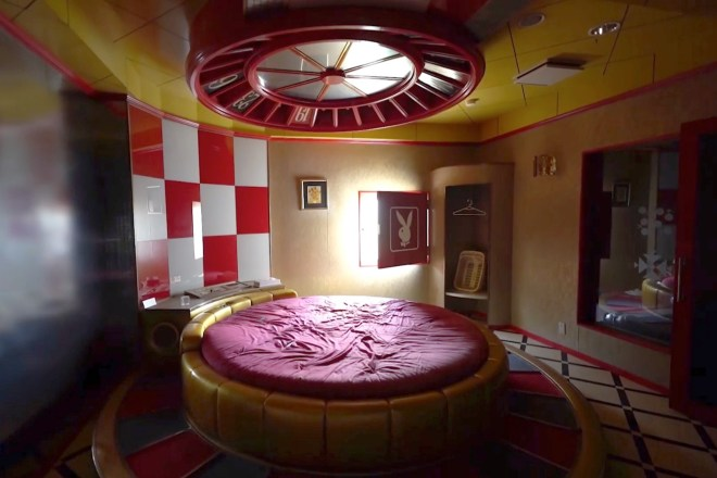 A casino themed room with a roulette wheel above the bed
