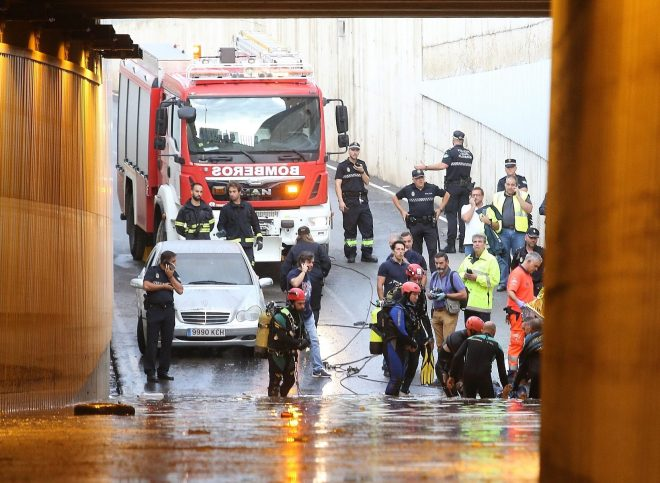 Firefighters recover the body of the driver from the flooded tunnel