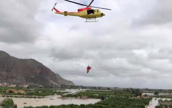 A rescue helicopter lowers down a rescuer to help save a person stranded on a roof