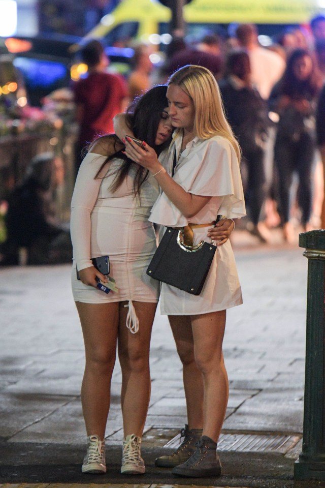 A woman looks at her phone whilst hugging her mate on Broad Street in Birmingham