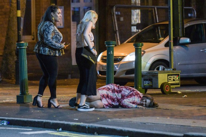 A woman is all smiles as she takes a rest on the pavement of Broad Street in Birmingham