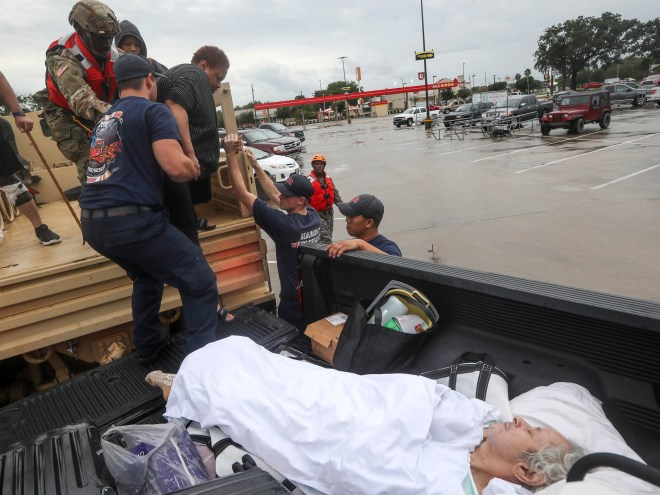 Dwain Kaufman, right, waits for his wife as she is helped into the back of a family member's truck by Beaumont firefighters