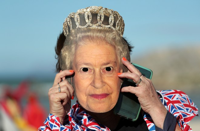 A fan holds up a mask of the Queen's face